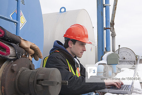 Engineer recording data on a laptop near a fuel tankers site in winter