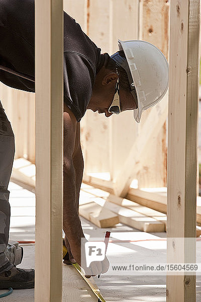 Carpenter measuring with a tape measure at a construction site