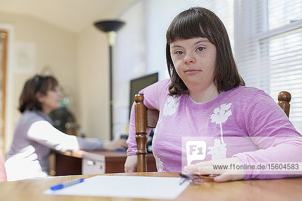 Girl with Down Syndrome sitting on chair with her mother using computer in the background