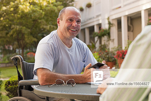 Businessman with Friedreich's Ataxia text messaging on a mobile phone with hand degeneration