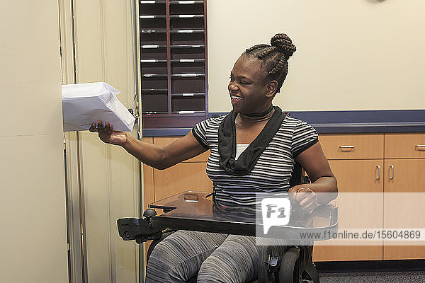 Teen with Cerebral Palsy getting copy paper