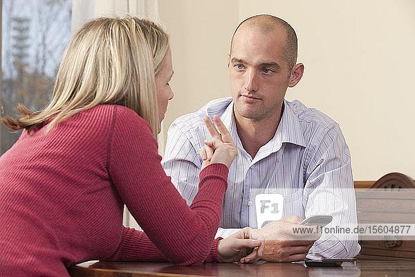 Frau gebärdet den Satz Look at me in amerikanischer Zeichensprache  während sie mit einem Mann kommuniziert