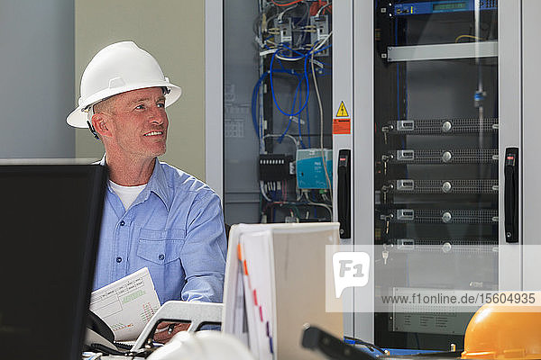 Electrical engineer working with switches and servers in broadband communication hub