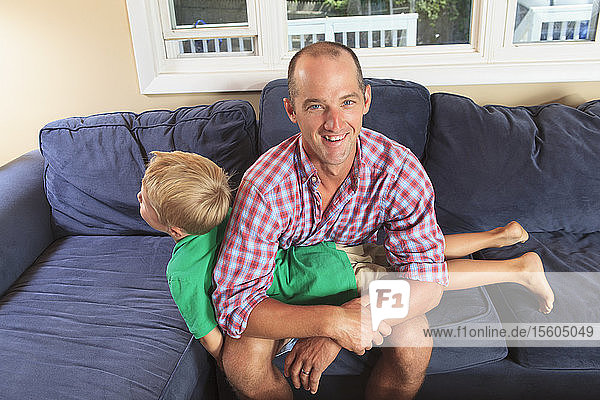 Father and son with hearing impairments playing on the couch
