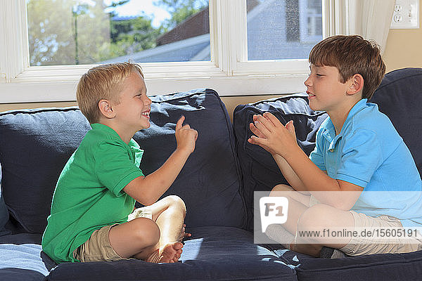 Boys with hearing impairments signing 'where  football' in American sign language on their couch