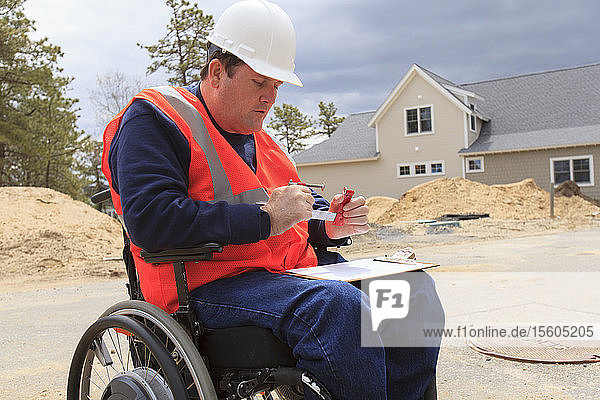 Construction engineer with spinal cord injury adjusting vise tool on site