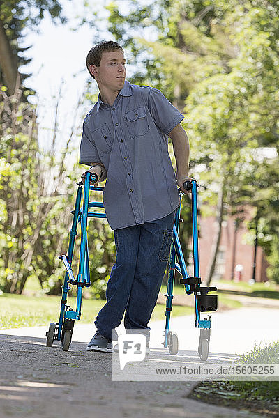 Young man with Cerebral Palsy using his walker to walk to work