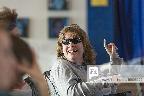 Woman with Cerebral Palsy and Visual impairment talking with other people in a meeting