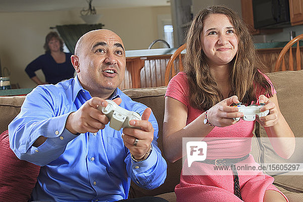 Father and daughter playing video games on their TV screen