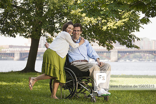 Pregnant woman hugging her husband in a wheelchair with a spinal cord injury