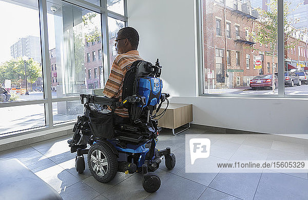 Man with Guillain-Barre Syndrome on wheelchair looking out through the apartment window