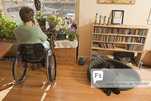 Woman with multiple sclerosis in a wheelchair talking on a mobile phone with service dog sitting near her