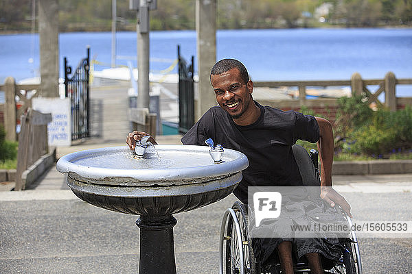 Man who had Spinal Meningitis in a wheelchair drinking from a fountain
