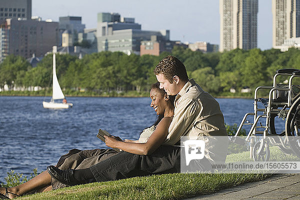 Couple sitting in a park and reading a book.