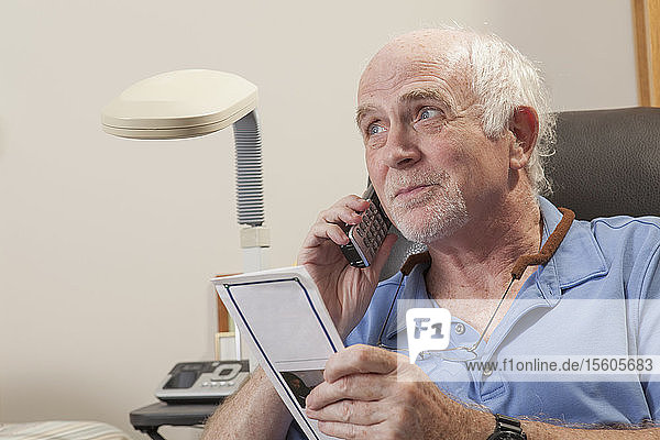 Man with Ataxia reading book and using his cell phone