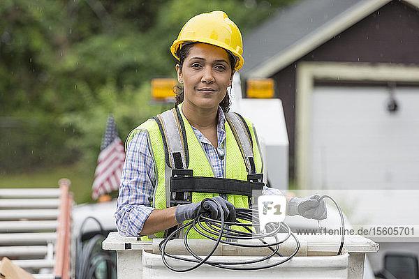 Hispanic female cable lineman in lift bucket