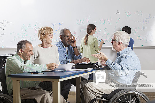 Faculty meeting in an engineering school  one professor with a spinal cord injury and one with Muscular Dystrophy