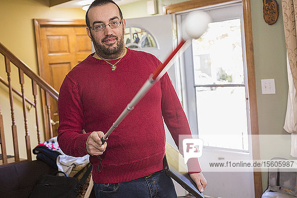 Man who has Visual Impairment with his cane at home