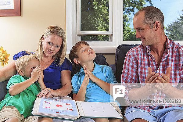Family with hearing impairments looking at a photo album and signing 'book' in American sign language on their couch