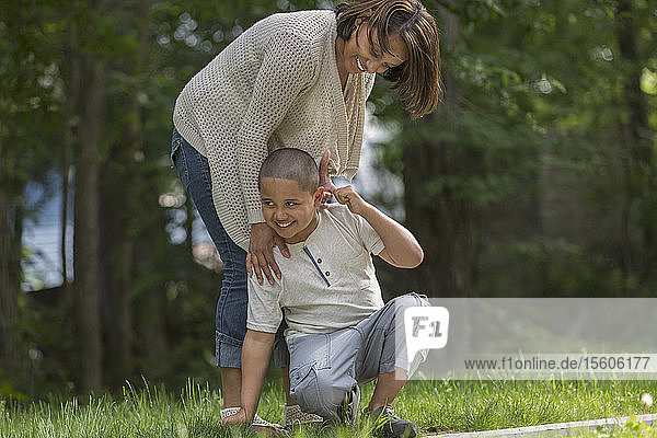 Hispanic boy with Autism playing outside with his mother