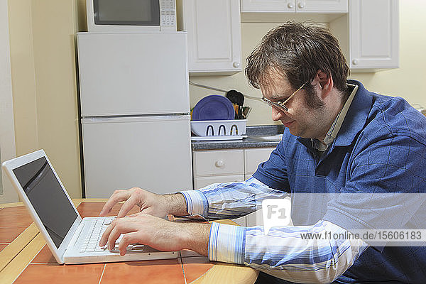 Technology engineer and programmer with Asperger's working on his laptop from home