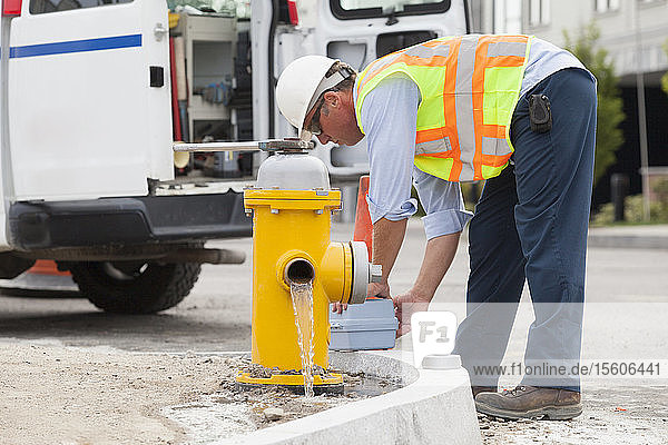 Department of public works engineer draining a hydrant and preparing to take a water sample