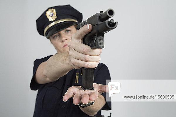 Police woman loading a pistol.