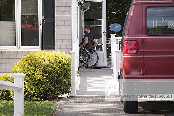 Man with spinal cord injury in a wheelchair going up home ramp