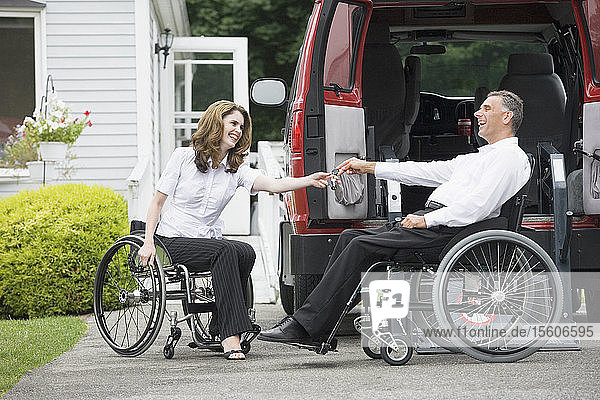 Mid adult woman giving a car key to a mid adult man sitting in a wheelchair with a Spinal Cord Injury