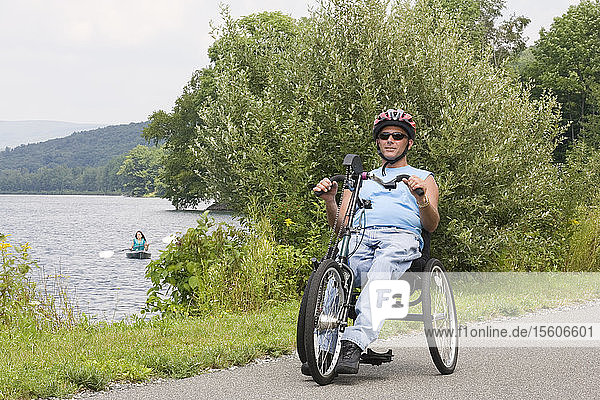 Young man with a Spinal Cord Injury riding adaptive bike with a young woman kayaking in a lake in the background