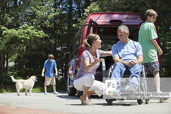 Man with spinal cord injury in wheelchair enjoying his family