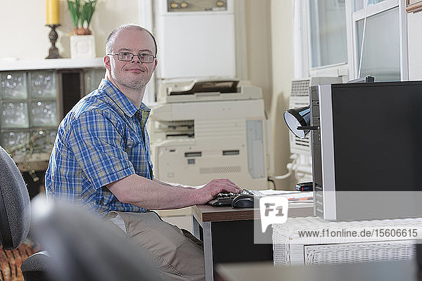 Man with Down Syndrome working at a computer in an office