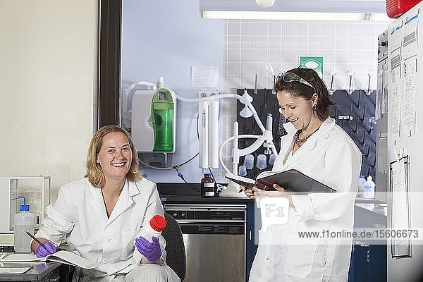 Two laboratory scientists recording chemical analysis data in a laboratory