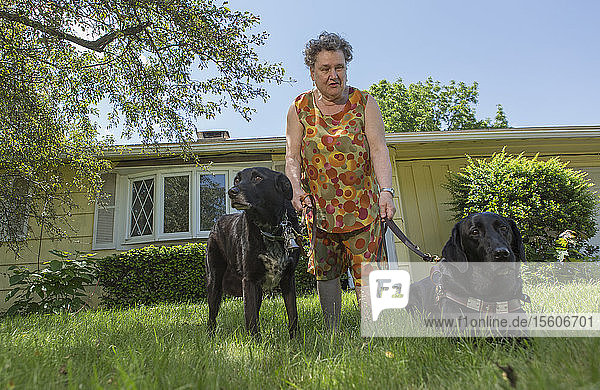 Blind senior woman with her service dogs in front of her house