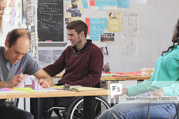 Engineering students actively brainstorming in ideation lab  one man with spinal cord injury and other one with Aspergers