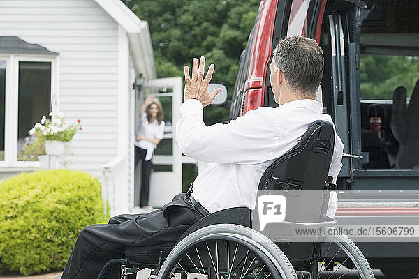 Side profile of a mature man sitting in a wheelchair with a Spinal Cord Injury and waving his hand