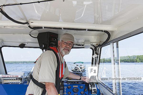 Public works engineer piloting service boat for sampling water on public reservoir