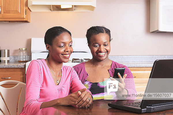Two sisters working with smartphone and laptop at home  one with learning disability