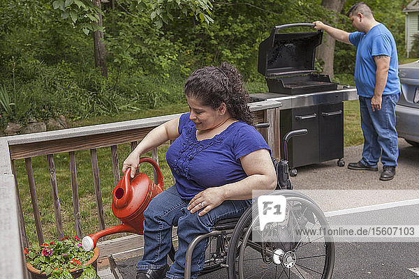 Woman with Spina Bifida watering their flowers with her husband in the background