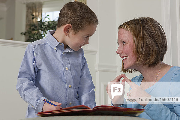Woman signing the word 'Word' in American Sign Language while teaching her son