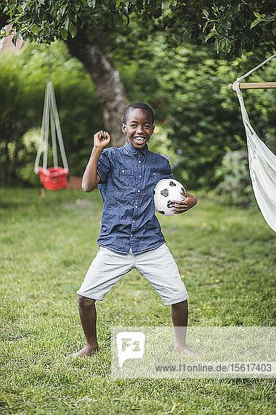 Lächelnder Junge tanzt in voller Länge  während er einen Fußball im Hinterhof hält