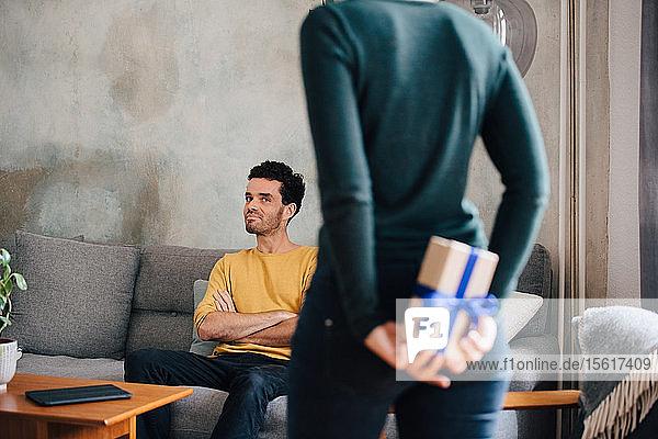 Mittelgroßer erwachsener Mann betrachtet Freundin  die eine Geschenkschachtel versteckt  während er im Wohnzimmer steht