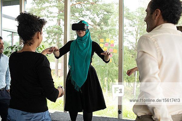 Geschäftsfrau hält Hand eines Kollegen  der einen Virtual-Reality-Simulator trägt  während der Eröffnungssitzung im Kongresszentrum