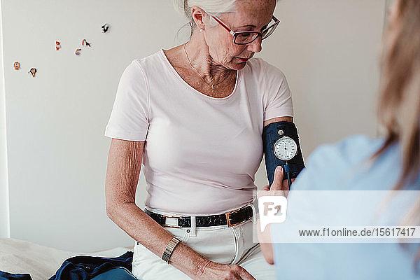 Ärztin prüft Blutdruck einer älteren Frau im Krankenhaus