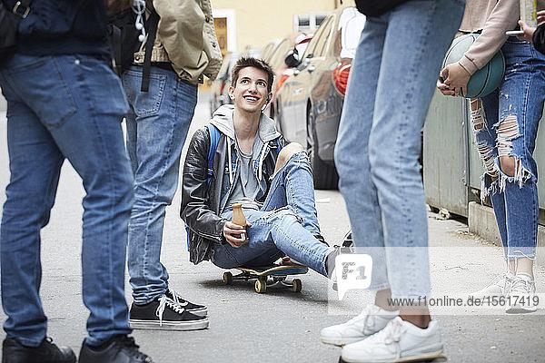 Niedrige Sektion von Freunden steht neben einem lächelnden Teenager  der auf einem Skateboard sitzt
