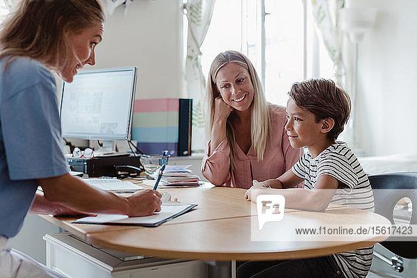 Mutter und Sohn konsultieren eine Kinderärztin am Schreibtisch in der Klinik