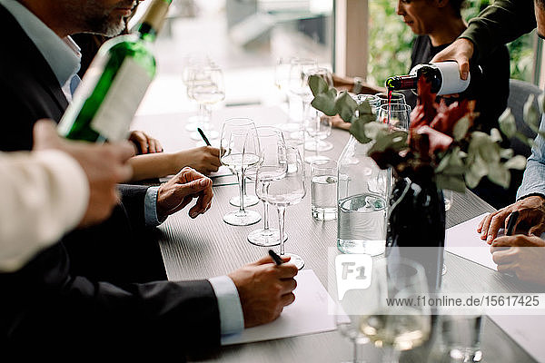 Male and business professionals with red wine at table in convention center