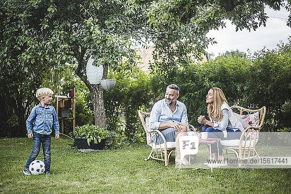 Eltern sehen Jungen beim Fußballspielen im Garten
