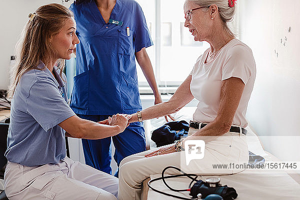 Doctor checking pulse of senior woman in medical examination room