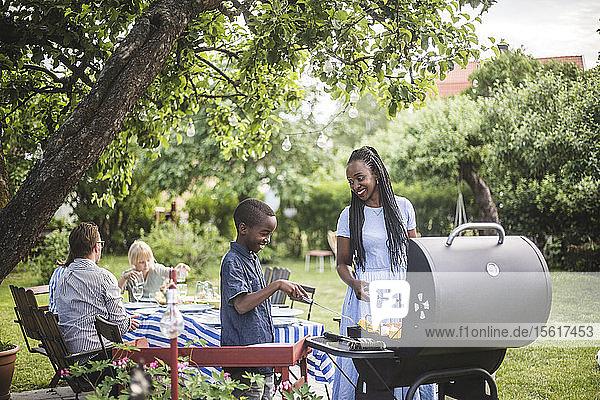 Mutter und Sohn bereiten während der Wochenendparty Essen auf dem Grill im Hof zu